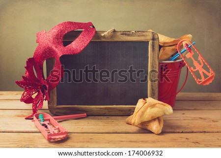 Hamantaschen cookies in bucket with grogge, chalkboard and carnival mask - stock photo