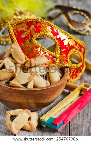 Hamantaschen cookies or Haman's ears, noisemaker and carnival masks for Purim celebration (jewish holiday). - stock photo