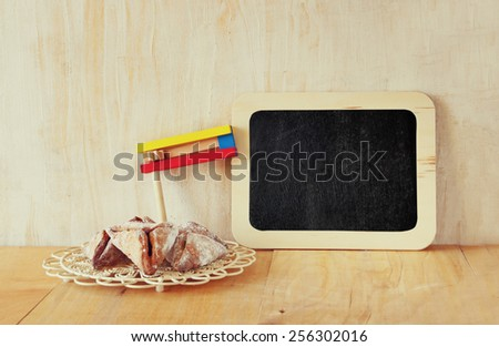 Hamantaschen cookies or hamans ears and noisemaker or gragger (jewish holiday). retro filtered image  - stock photo
