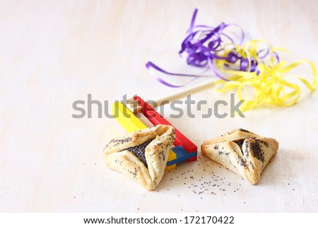 Hamantaschen cookies or hamans ears for Purim celebration and noisemaker over textured wooden board - stock photo