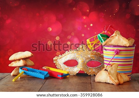 Hamantaschen cookies or hamans ears,noisemaker and mask for Purim celebration (jewish carnival holiday) and glitter background. selective focus  - stock photo