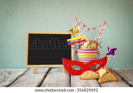 Hamantaschen cookies or hamans ears,noisemaker and mask next to blackboard for Purim celebration (jewish carnival holiday). selective focus - stock photo