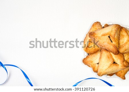 Hamantaschen or Haman's ears - triangular cookies for Jewish holiday of Purim, on light background  - stock photo