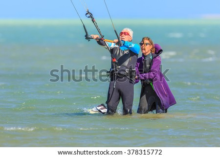 HAMATA, EGYPT - DECEMBER 05, 2015: Woman instructor  teaches the old man  engaged in kite surfing