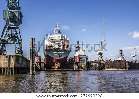 HAMBURG, GERMANY - APRIL 19, 2015: A big containership is lying in the drydock, in the harbor of Hamburg, Germany. Cranes and other industrial machinery is around. - stock photo