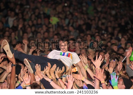 HAMBURG, GERMANY - AUGUST 15, 2014: German DJ and producer ALLE FARBEN doing a stage dive at MS Dockville Festival on August 15, 2014 in Hamburg. - stock photo