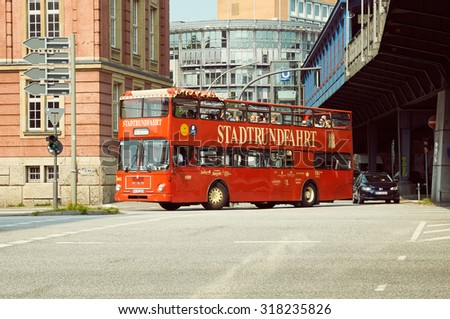 HAMBURG, GERMANY - AUGUST 14, 2015: Red city sightseeing bus with tourists at the city street. - stock photo
