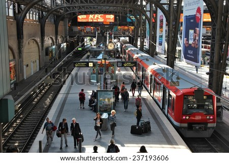 HAMBURG, GERMANY - AUGUST 28, 2014: Travelers board the train at Central Railway Station (Hauptbahnhof) in Hamburg. With 450,000 daily passengers it is the 2nd busies station in Europe. - stock photo
