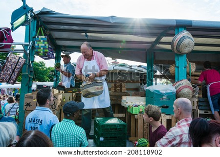 Hamburg, Germany - July 20, 2014: A greengrocer is selling fruit on the traditional Hamburg Fish Market  in the early Sunday Morning on July 20, 2014 in Hamburg, Germany. The Fish Market is active - stock photo