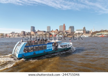 HAMBURG, GERMANY - MARCH 20, 2014: Harbor ferry passes before the skyline of St. Pauli, Hamburg, Germany on March 20, 2014. - stock photo