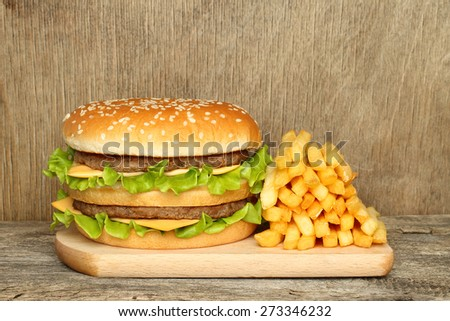 Hamburger and french fries on old wooden background - stock photo