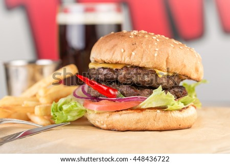 Hamburger and glass of beer on wooden table - stock photo