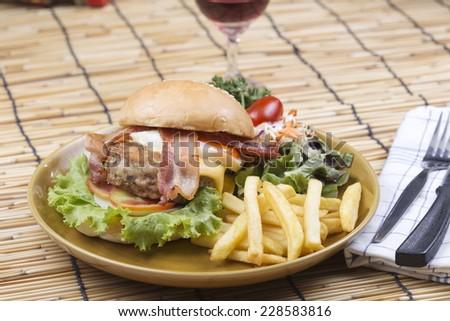 hamburger beef bacon egg french fries and salad  - stock photo
