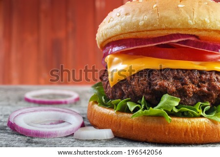 Hamburger closeup with red onions , red wood wall background with copyspace - stock photo