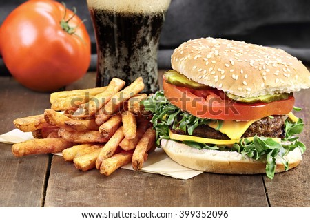 Hamburger, fries and soda over rustic background. Selective focus with extreme shallow depth of field. - stock photo