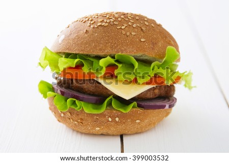Hamburger, homemade hamburger with fresh vegetables  on rustic wooden table surface  - stock photo