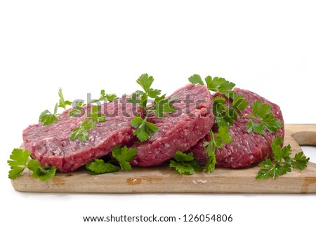 Hamburger of beef on wooden board with parsley