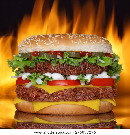 Hamburger on black background with reflection and real fire on back - stock photo