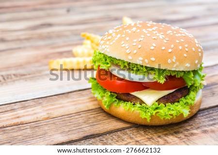 Hamburger on wood table ,sun flare filter effect - stock photo