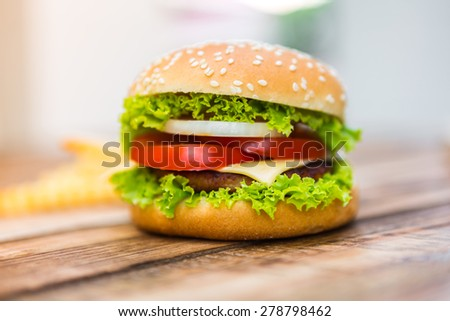 Hamburger on wood table ,sun flare filter effect