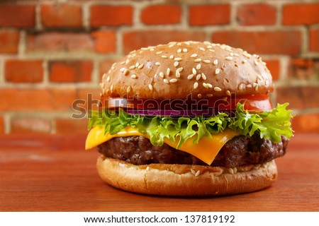 Hamburger on wooden table with red brick wall background - stock photo