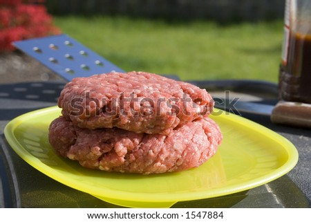 Hamburger Patties ready for the grill. Photo shot with spatula and barbecue sauce. - stock photo