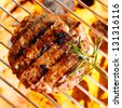 Hamburger patty on the grilling pan with open flames - stock photo