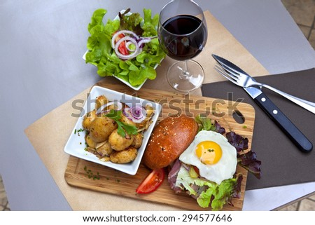 Hamburger, potatoes, green salad and a glass of red wine - stock photo