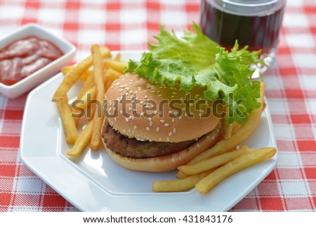 Hamburger served with french fries, ketchup, drink on red napkin