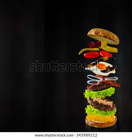 Hamburger stacked high with a juicy beef patty, cheese, fresh lettuce, onion and tomato with flying ingredients, space for text - stock photo