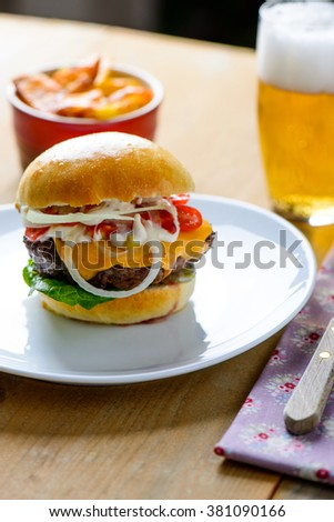 Hamburger with beer and fries in the background ready to be eaten - stock photo