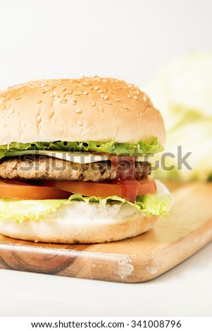 Hamburger with cheese and ingredients with a white background and timber board.