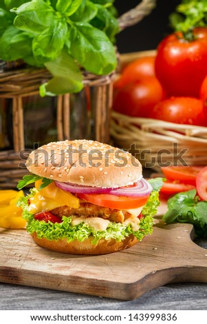 Hamburger with chicken, tomato and vegetables - stock photo