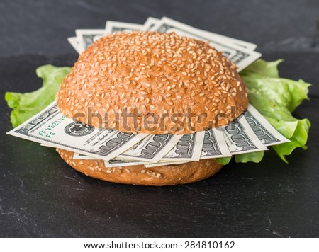 Hamburger with dollar bank notes on black background - stock photo
