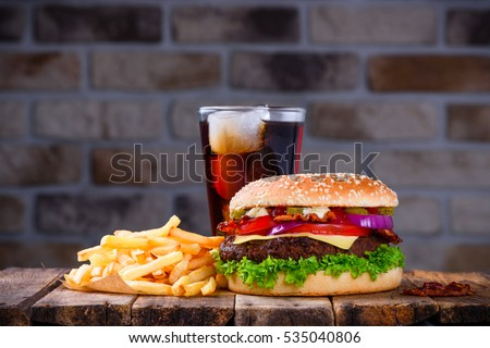 Hamburger with french fries and cola on wooden table