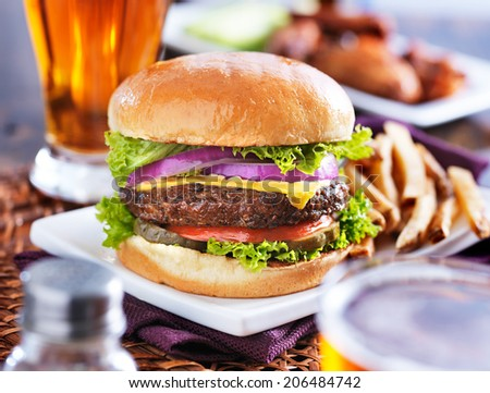 hamburger with fries and beer shot in panorama style with chicken wings in background - stock photo