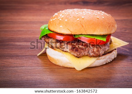 Hamburger with grilled beef, cheese and vegetables - stock photo