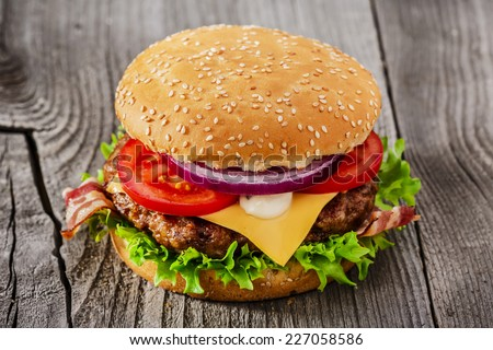 hamburger with grilled meat cheese bacon on a wooden surface - stock photo