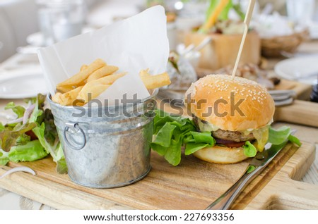 Hamburger with juicy beef and cheese with potato and vegetables salad - stock photo