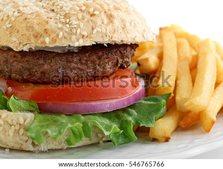 Hamburger with lettuce, tomato, and onion on sesame bun with french fries