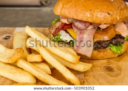 Hamburger with pork, beef, and vegetables is in the bread, overlapping layers.