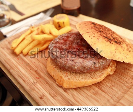 Hamburger with potato fries and corn on the wooden plate. - stock photo