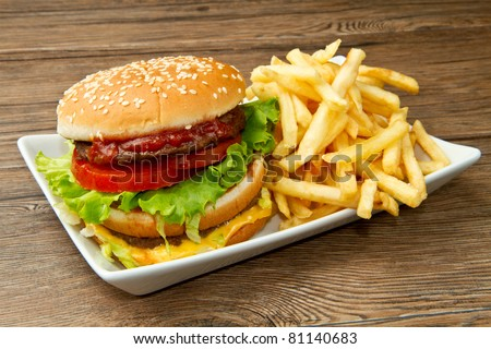 hamburger with potatoes on wooden background - stock photo