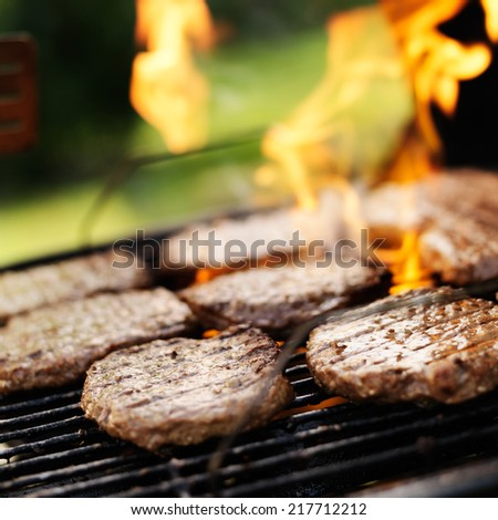 hamburgers grilling on charcoal grill - stock photo