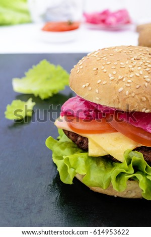 Hamburgers with juicy cutlet, tomatoes, pickled cabbage and cucumbers, cheese, green lettuce leaves and a soft bun with sesame on the black background