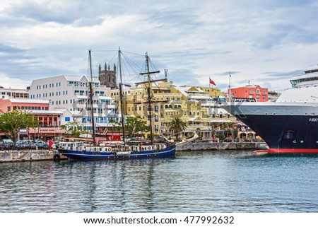 HAMILTON,BERMUDA, MAY 25 - A tall ship and a cruise ship docked with colorful buildings along Front St. on May 25 2016 in Hamilton,Bermuda.