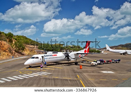 HAMILTON ISLAND, AUSTRALIA - OCTOBER 3,2015: Passengers board a QANTASLINK Bombardier Dash-8 aircraft. Hamilton Island is the only island on the Great Barrier Reef with its own airport. - stock photo