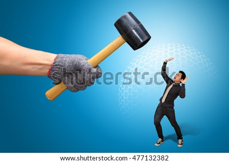 Hammer Against Business Man with barrier