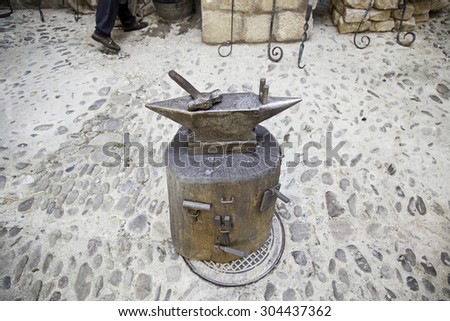 Hammer and anvil, detail of a forge, metal tools - stock photo