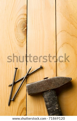 Hammer and nails isolated on wooden background - stock photo